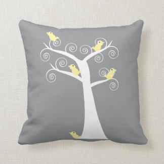 Cinco pájaros amarillos en un árbol soportan cojin