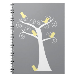 Cinco pájaros amarillos en un cuaderno del árbol