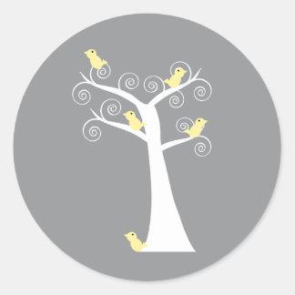 Cinco pájaros amarillos en un pegatina del árbol