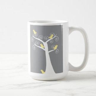 Cinco pájaros amarillos en una taza del árbol