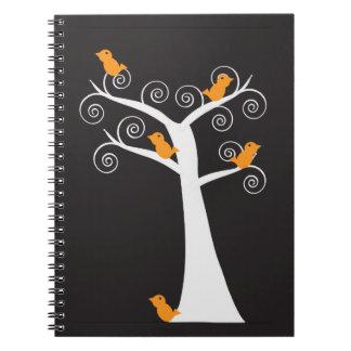 Cinco pájaros anaranjados en un cuaderno del árbol