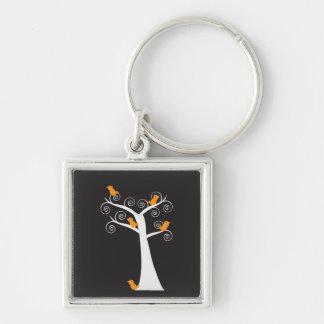 Cinco pájaros anaranjados en un llavero del árbol