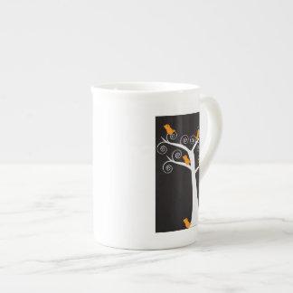 Cinco pájaros anaranjados en una taza de la especi taza de porcelana