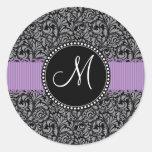 Cinta floral negra inicial de la púrpura del pegatina redonda