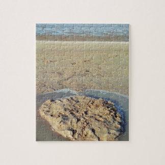 Círculo en arena en la playa, tiempo del agua de rompecabezas