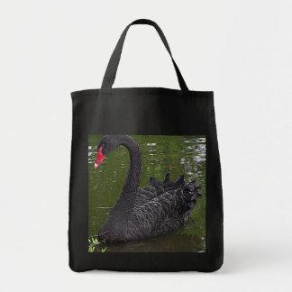Cisne negro magnífico en el agua bolsas