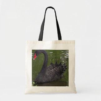 Cisne negro magnífico en el agua bolsas lienzo