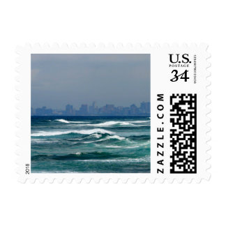 City Skyline behind the waves of the ocean Postage