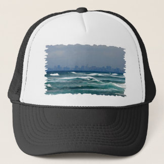 City Skyline behind the waves of the ocean Trucker Hat