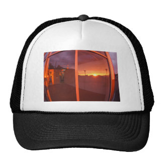 Cityscape at sunset, which is reflected in the win trucker hat