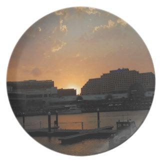 Ciudad oscura de la orilla de la puesta del sol plato de comida