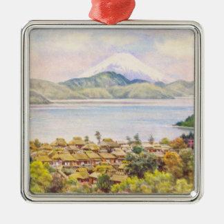 Ciudad por el lago cerca del paisaje del monte adorno navideño cuadrado de metal