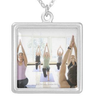 Clase principal del instructor de la yoga con colgante cuadrado