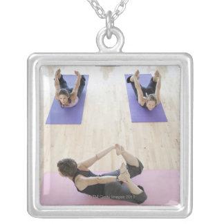 Clase principal del instructor de la yoga con los colgante cuadrado