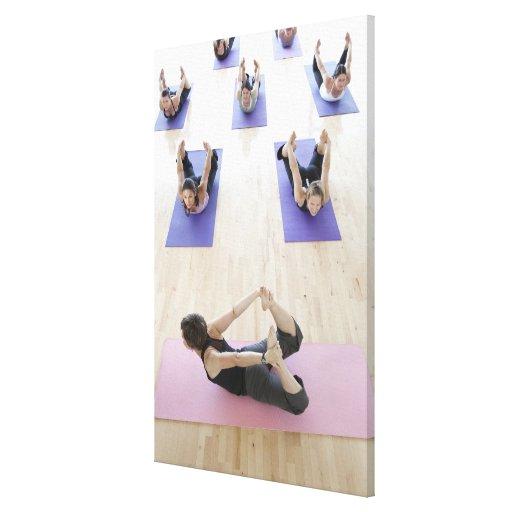 Clase principal del instructor de la yoga con los  lona envuelta para galerías