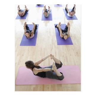 Clase principal del instructor de la yoga con los postal
