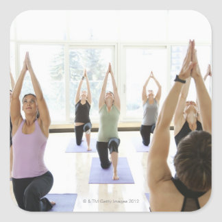 Clase principal del instructor de la yoga con colcomanias cuadradass
