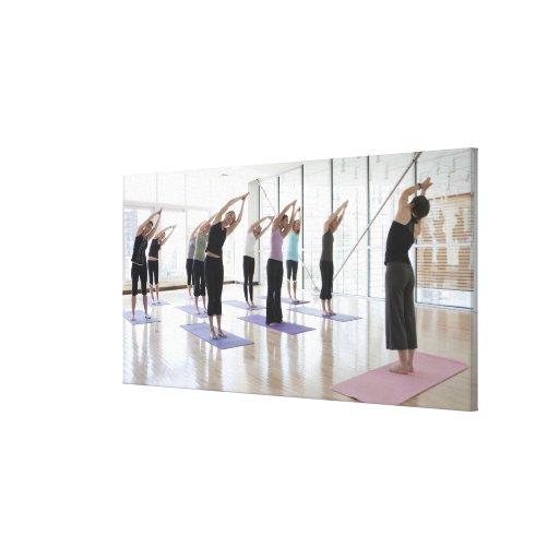 clasifique la yoga practicante con el instructor e impresión en lona estirada