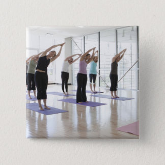 class practicing yoga with instructor in a 2 button