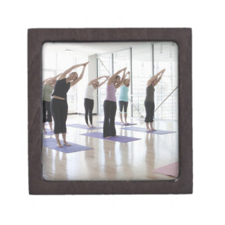 class practicing yoga with instructor in a 2 gift box
