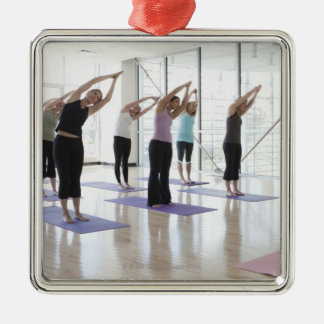 class practicing yoga with instructor in a 2 metal ornament