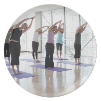 class practicing yoga with instructor in a 2 dinner plate