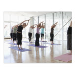 class practicing yoga with instructor in a 2 postcard