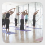 class practicing yoga with instructor in a 2 square sticker