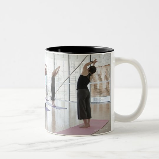 class practicing yoga with instructor in a 2 Two-Tone coffee mug