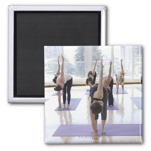 class practicing yoga with instructor in a fridge magnet