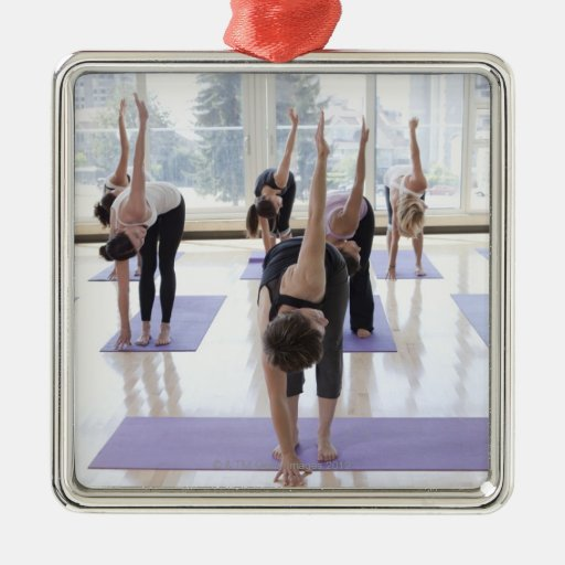 class practicing yoga with instructor in a metal ornament