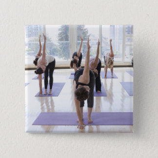 class practicing yoga with instructor in a pinback button