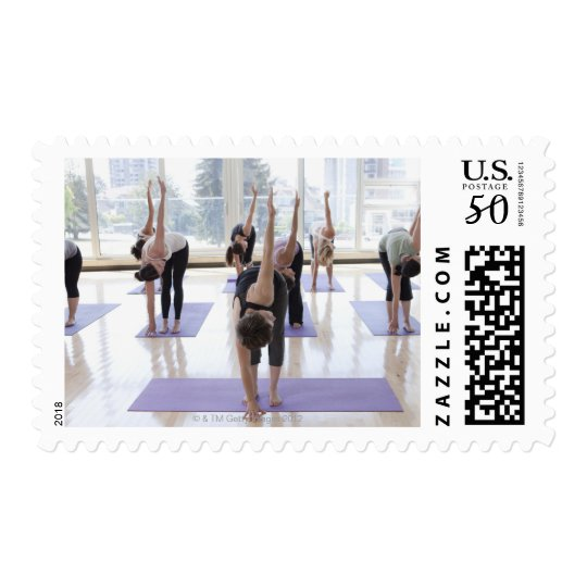 class practicing yoga with instructor in a postage