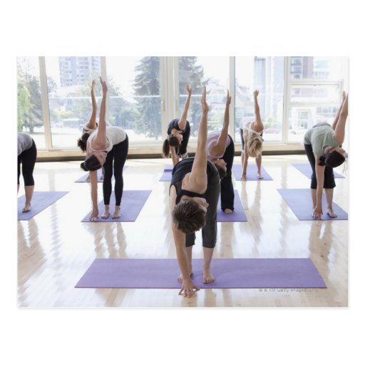 class practicing yoga with instructor in a postcard