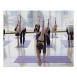 class practicing yoga with instructor in a poster