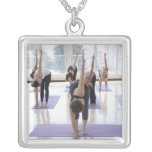 class practicing yoga with instructor in a square pendant necklace