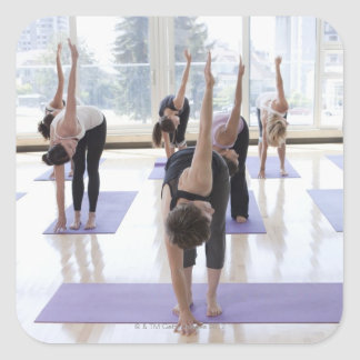 class practicing yoga with instructor in a square sticker