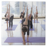 class practicing yoga with instructor in a ceramic tiles