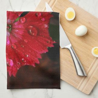 Clavel rojo con las gotas de agua toallas