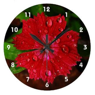 Clavel rojo con las gotas de agua reloj redondo grande