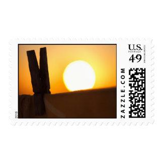 Clavija de ropa en la salida del sol timbre postal