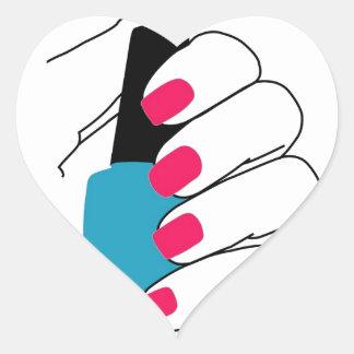 Clavos con un esmalte de uñas a disposición pegatina en forma de corazón