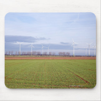 Clean energy by many wind turbines on fields. mouse pad
