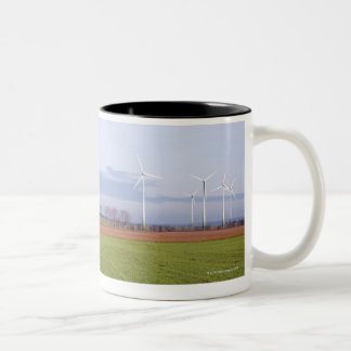 Clean energy by many wind turbines on fields. coffee mug