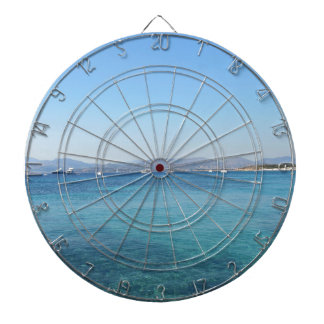Clear turquoise sea water and boats on the horizon dartboard with darts