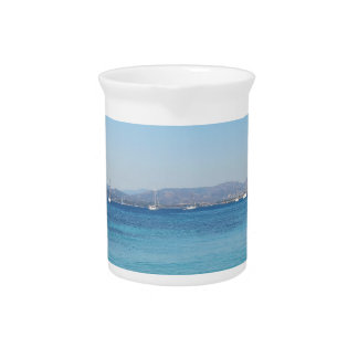 Clear turquoise sea water and boats on the horizon drink pitcher