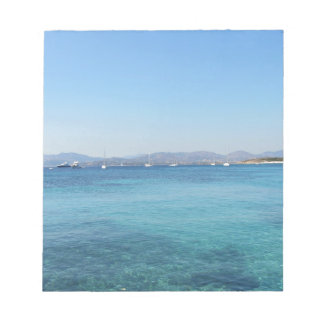 Clear turquoise sea water and boats on the horizon notepad
