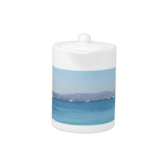 Clear turquoise sea water and boats on the horizon teapot