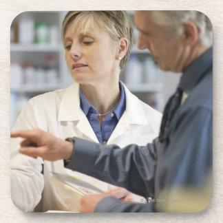 Cliente de ayuda del farmacéutico con la medicina posavasos de bebida