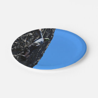 Climber scales face of mountain paper plate